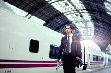 Businessman walk on the platform of big railway station