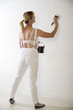 Woman in overalls painting a wall white