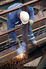 Welder using cutting torch to cut an old iron bridge