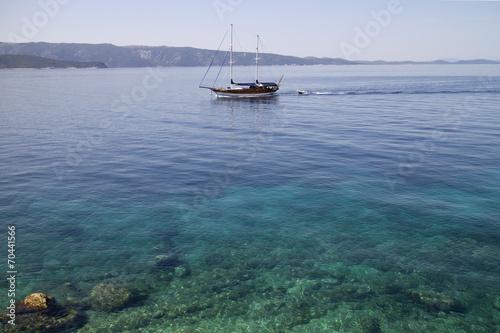 Leinwanddruck Bild Wooden sailing boat with two masts near coastline of Brac island