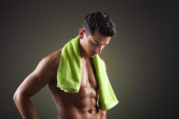 Athletic man with a green towel on black background