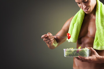 Smiling fitness man holding a bowl of fresh salad on black backg