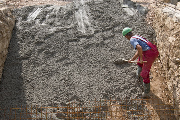 Worker in red and green boots flattens concrete with rake