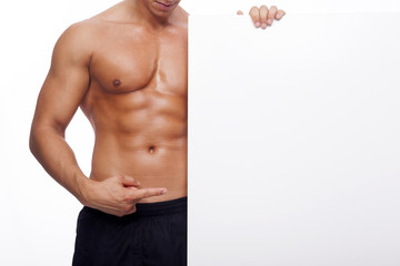 Fitness man pointing to a white banner