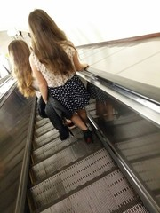 Two young women on the escalator