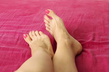 female foots with red nails on the red sheets
