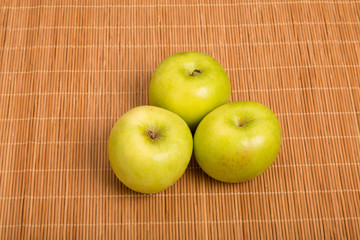 Three Granny Smith Apples on a Bamboo Placemat