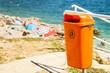 Leinwanddruck Bild - Trash can near the sea beach.