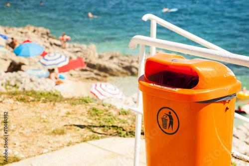 Leinwanddruck Bild Trash can near the sea beach.