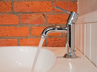 Water leaking from the tap with the old brick wall