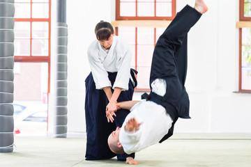 Aikido Lehrer und Schüler trainieren Werfen