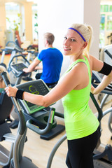 Group in gym on elliptical trainer