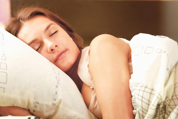 portrait of a cute young woman sleeping on the bed