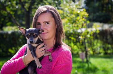 Portrait of positive brunette with pincher dog
