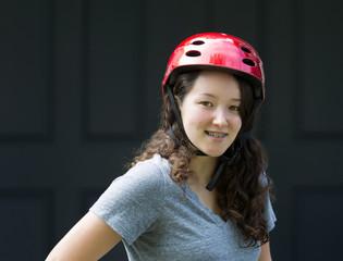 Teenage girl outdoors while wearing bicycle helmet