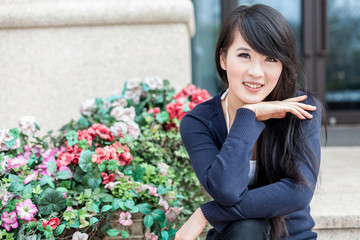 young asian women sits by the flower