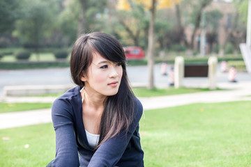 young asian woman sits on the grass field