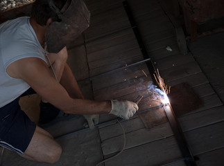 worker with protective gloves welding metal and sparks