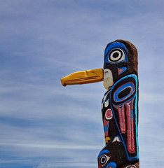 Old totem pole on the background of cloudy sky