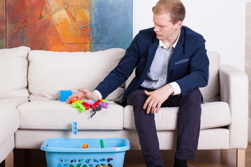 Businessman cleaning child's toys