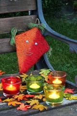 Herbstdeko auf Gartenbank, Kerze Blätter Drachen