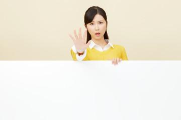 メッセージボードと制止する女性