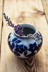 flowers are lavender with vase on wooden