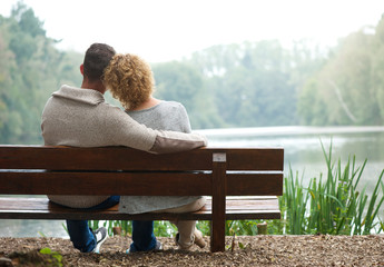 Rear view couple sitting on bench outdoors