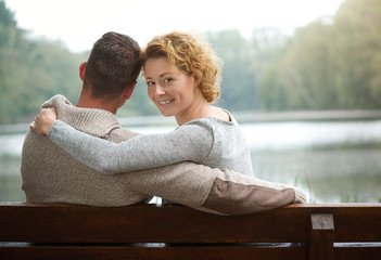 Couple sitting on bench by a lake