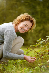 Smiling woman picking berries in the forest