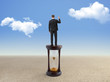Young businessman standing on hourglass