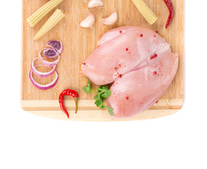 Raw chicken breast on wooden platter.