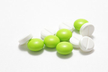 Green and white pills on white background