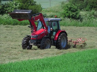 Red tractor mowing grass , agricultural labor