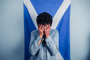 Depressed man standing in front of scottish flag
