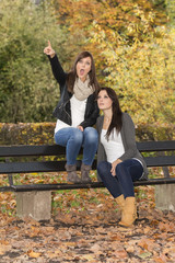 Two beautiful lifestyle women on a bench in colorful autumn