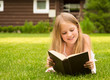 Beautiful smiling teenage girl lying on grass and read book
