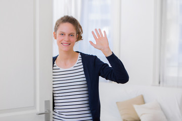 Young attractive woman welcoming you in his house
