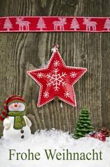 Weihnachtsstern aus Blech auf Holzwand mit Schnee