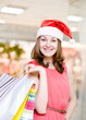 Beautiful Happy Girl With Red Hat and Shopping Bags In Shopping