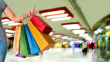 Woman holding shopping bags  and showing ok sign