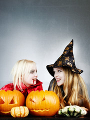 Little witch and vampire with pumpkins
