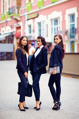 beautiful girls in black suits posing on the street