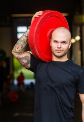 Fit Man Carrying Barbell Plate in Gym