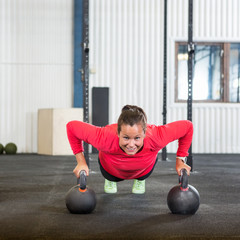 Woman Doing Pushup Exercise With Kettlebell