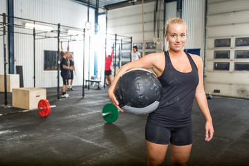 Confident Woman Carrying Medicine Ball