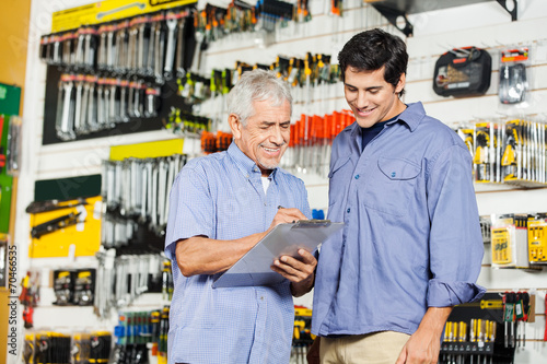 Customers Checking Checklist In Hardware Store - 70466535