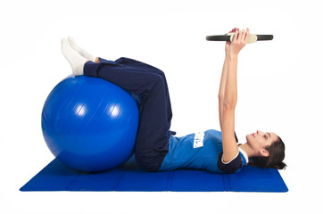 Young woman with blue fitness ball doing pilates