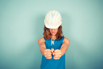 Young female builder holding pliers