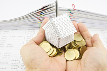 Man holding house on pile gold coins over finance account